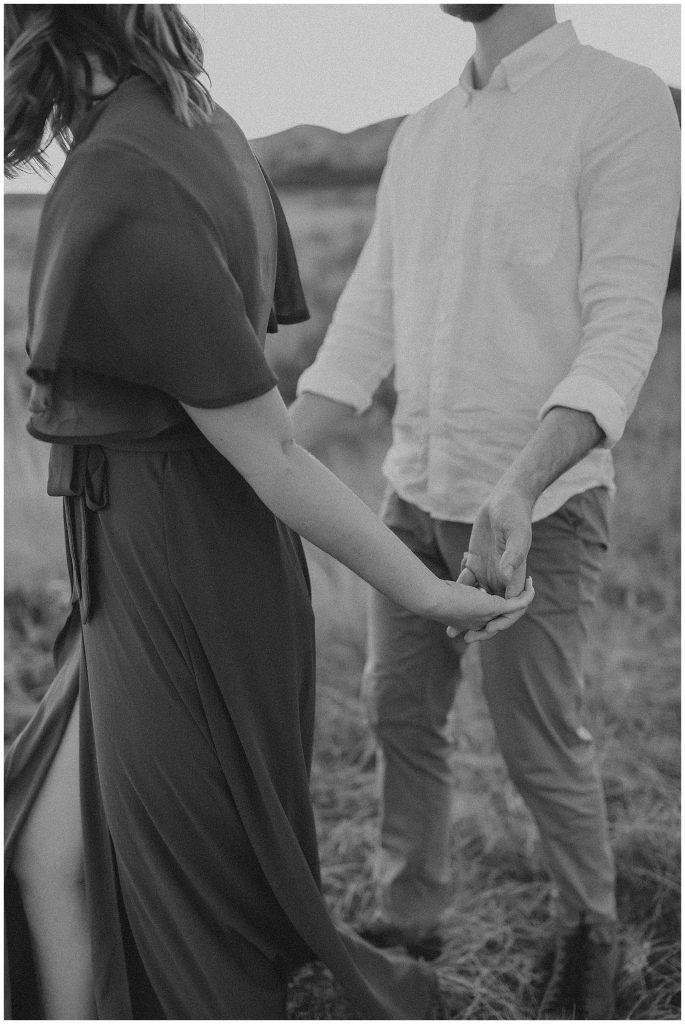 Black and white couple holding hands in a field at sunset