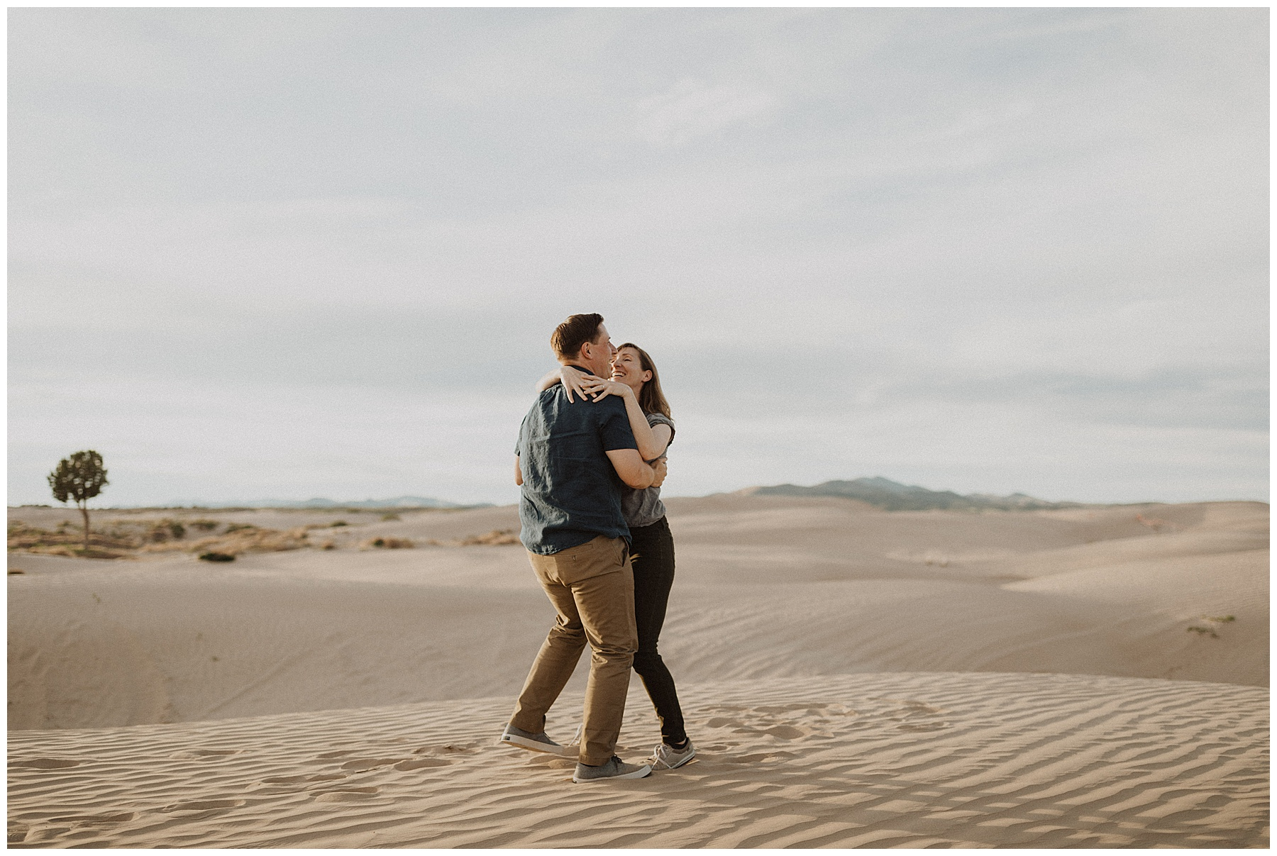 Couple hugging and spinning in Sand Dunes at Little Sahara in Utah