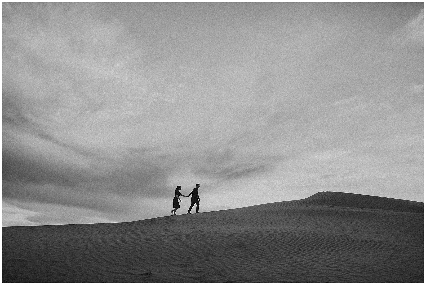 Silhouette black and white couple walking across sand dunes in Utah