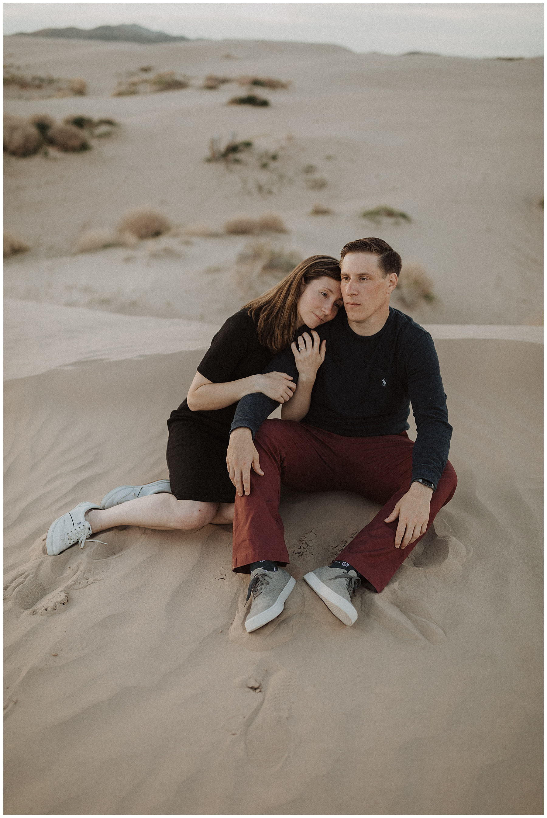Couple cuddling on the sand dunes at Little Sahara in Utah