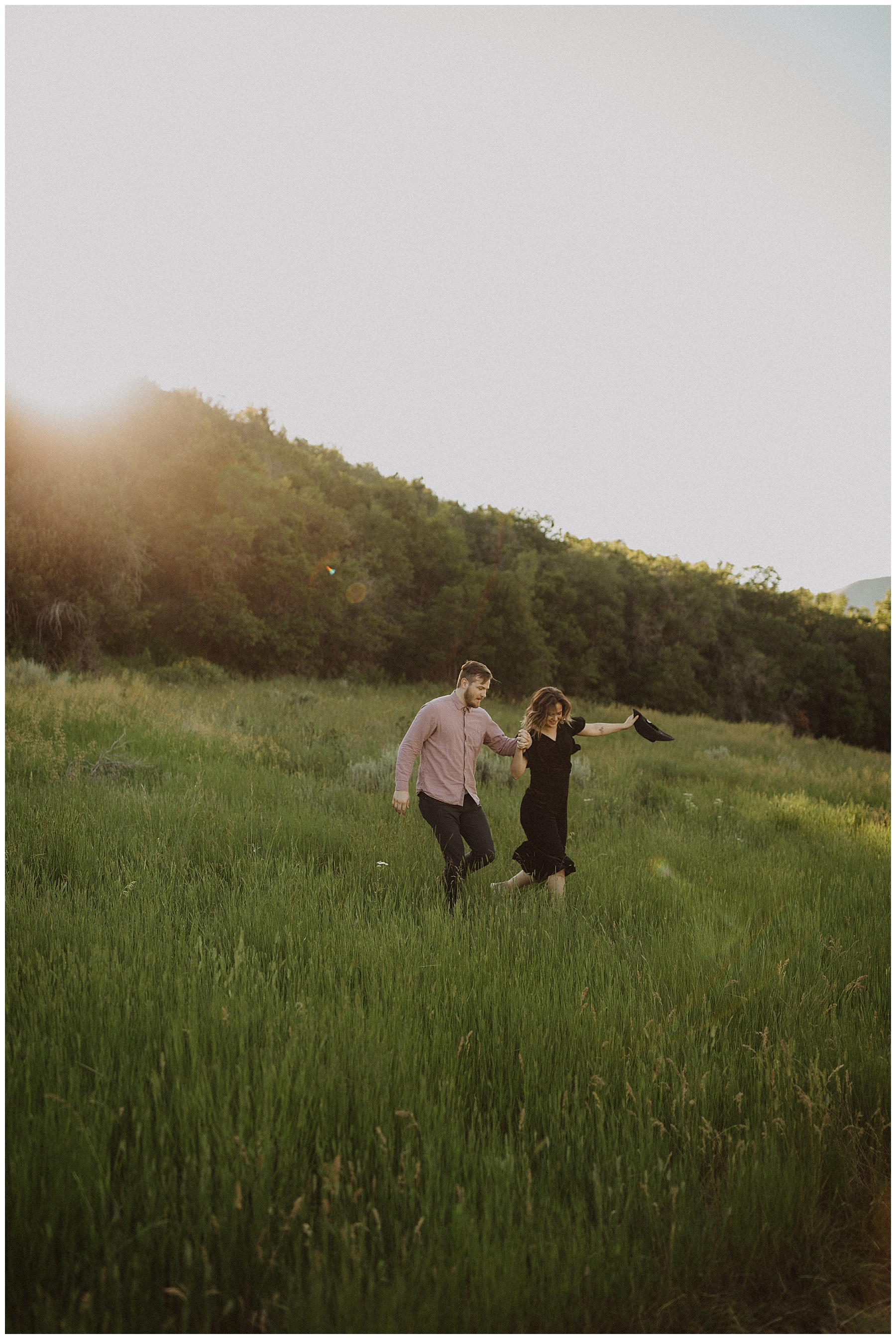 Couple running through a summer green field in Provo Canyon