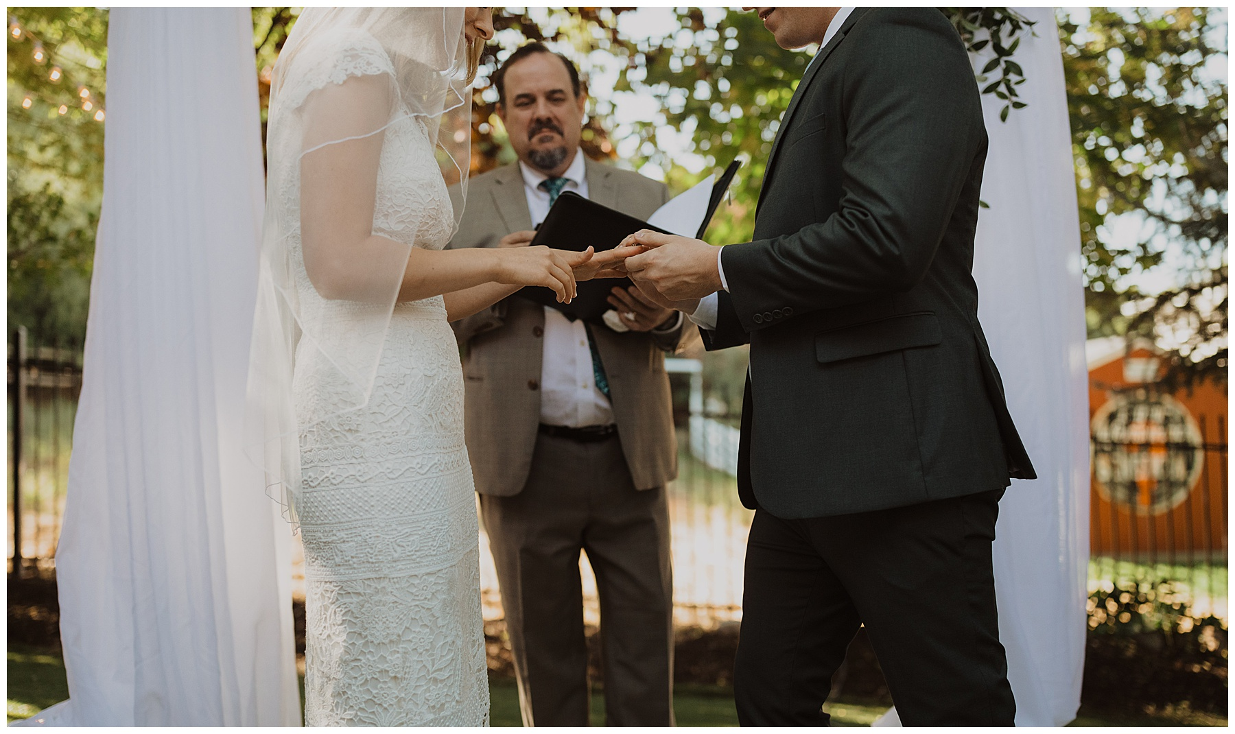 Bride and groom exchanging rings at a backyard wedding ceremony in the summer