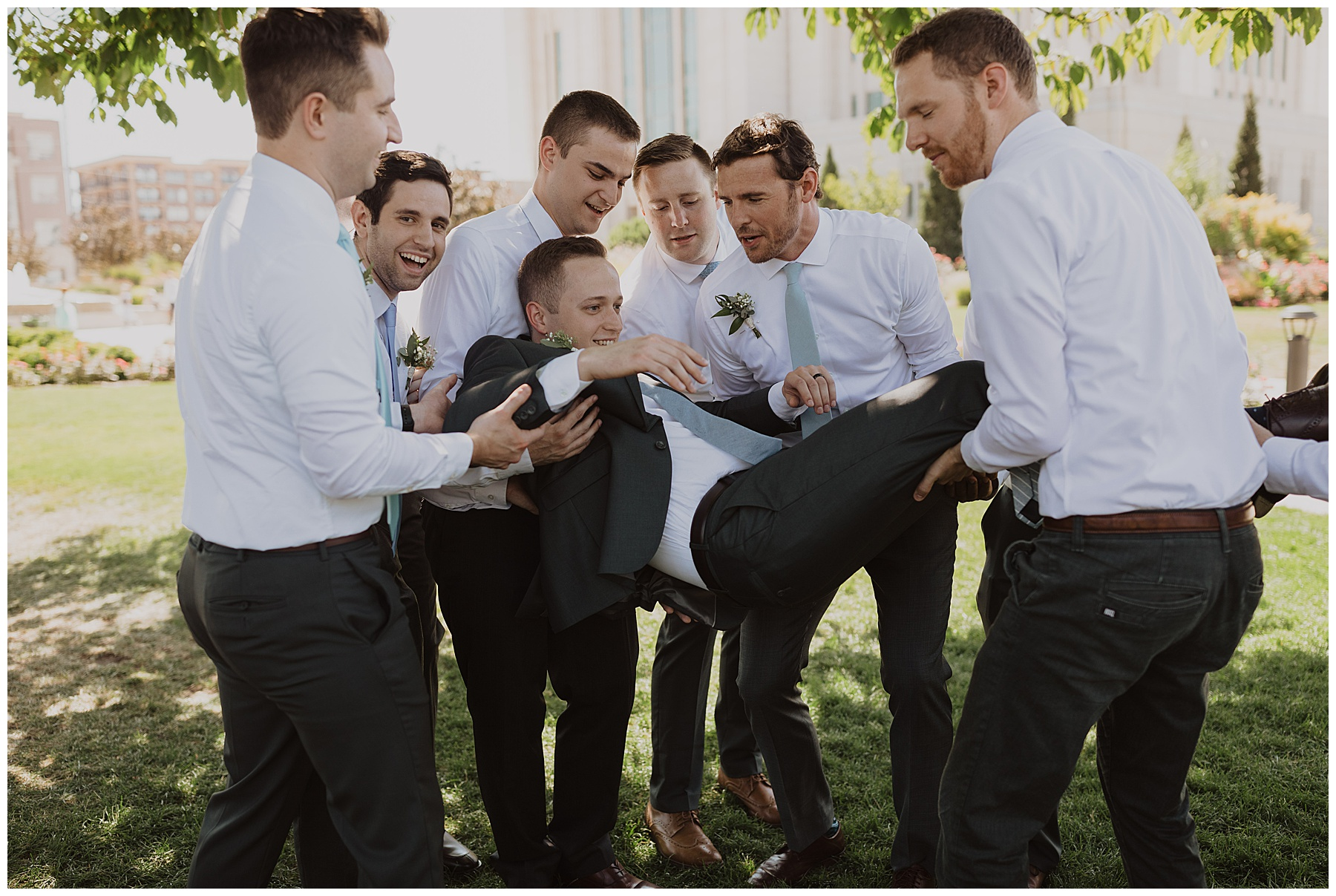 Groomsmen throw groom in the air after he is married