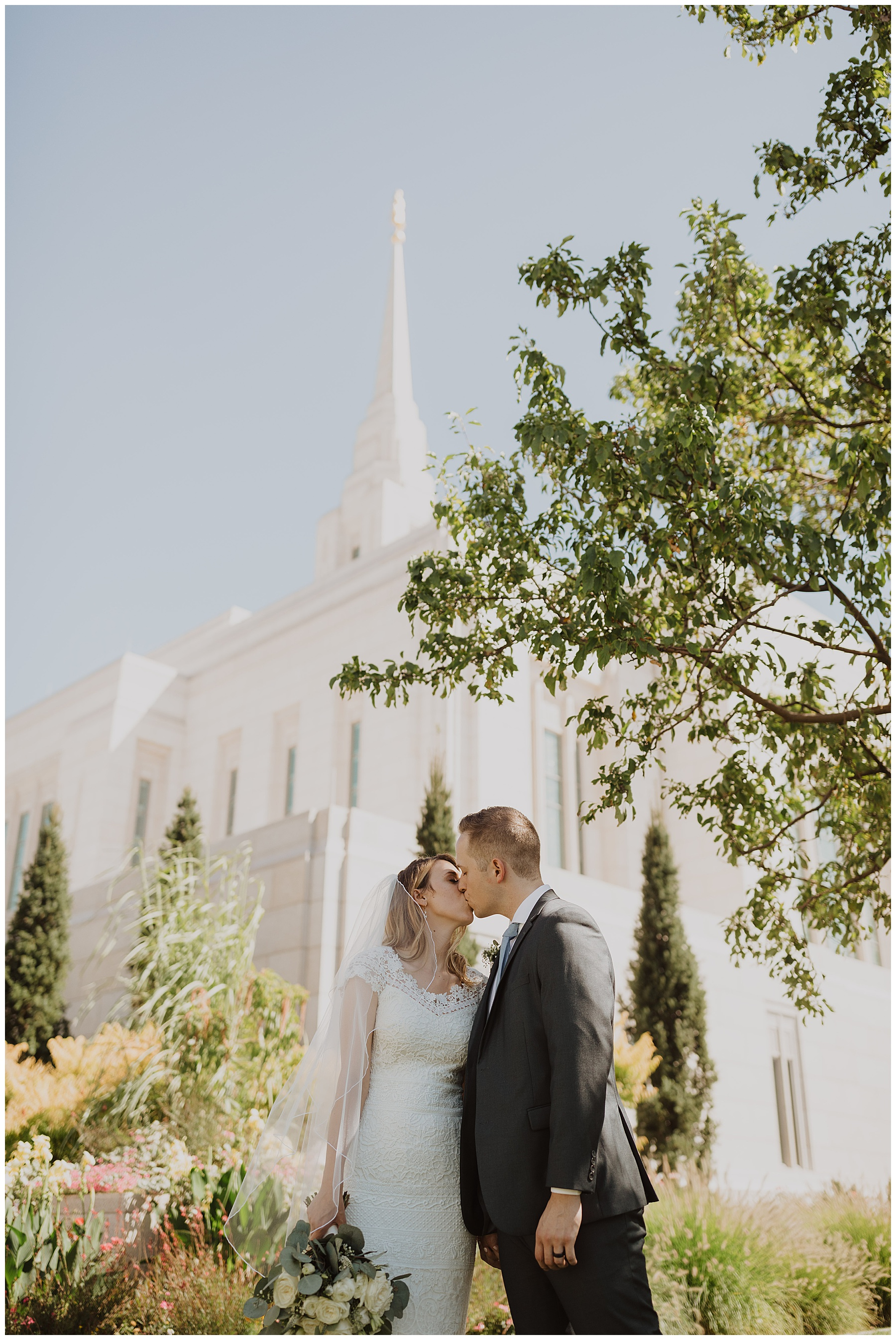 Bride and groom kiss in front of the Ogden Utah LDS Temple