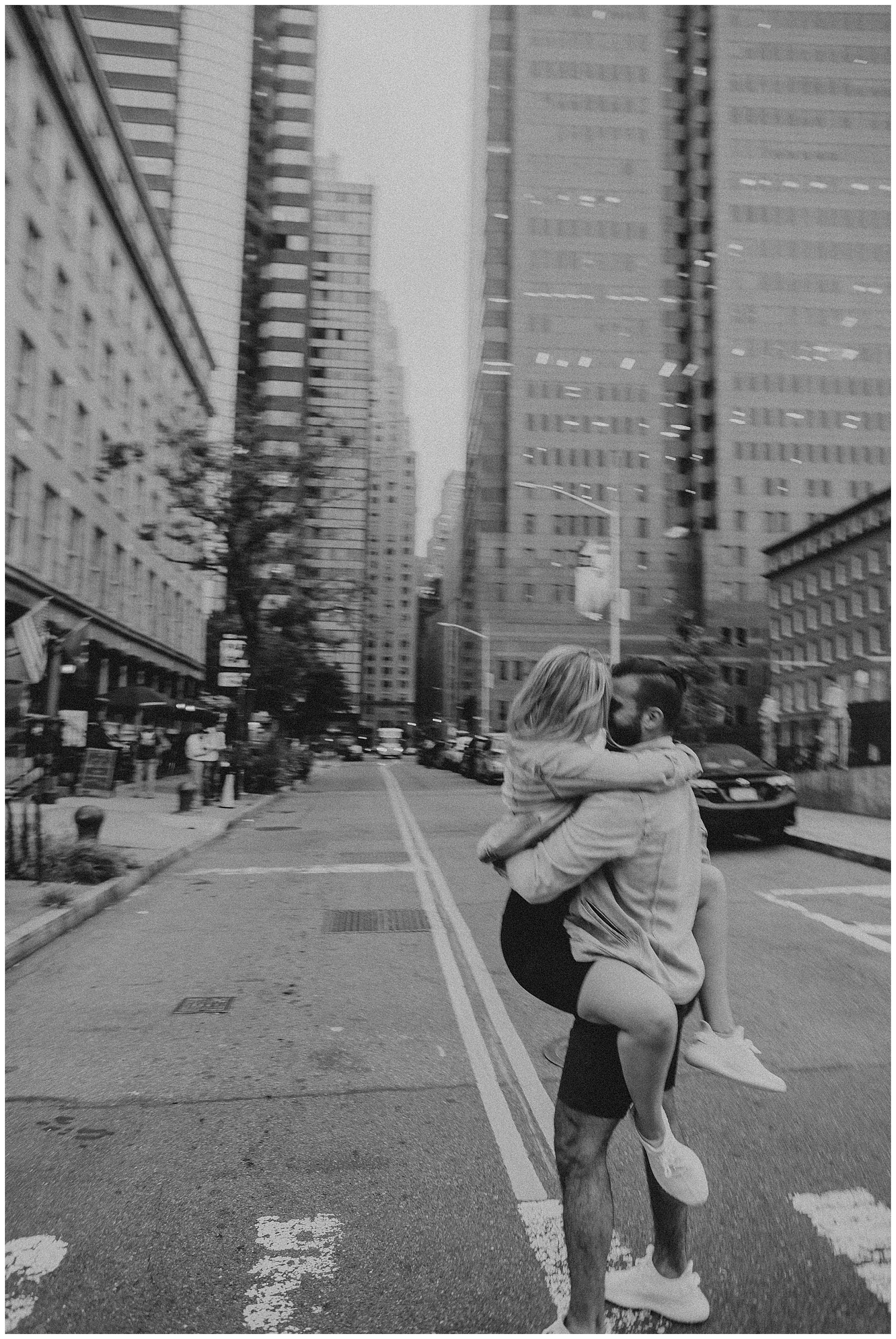 Couple hugging in a cross walk in New York City financial district