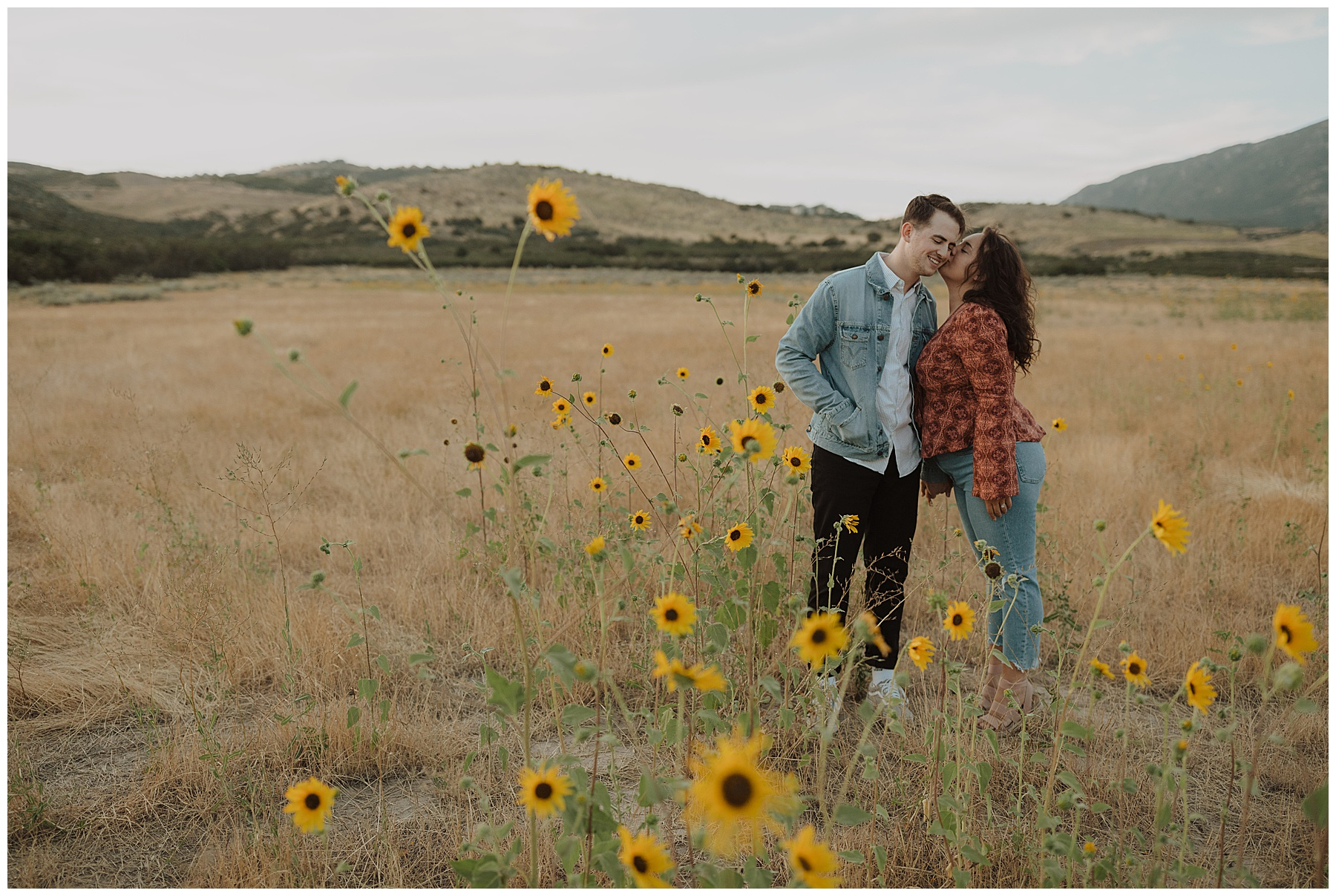 Couple kissing in front of sunflowers in the summer in Utah